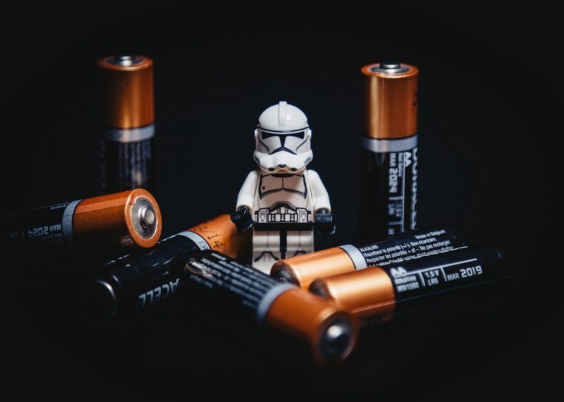 lego clone surrounded by 7 batteries, black background