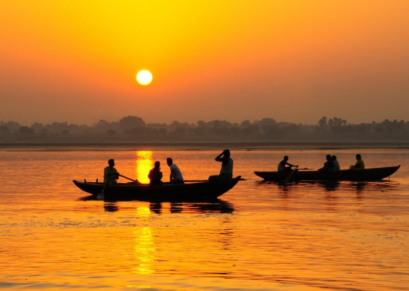 men in canoes in India during sunset