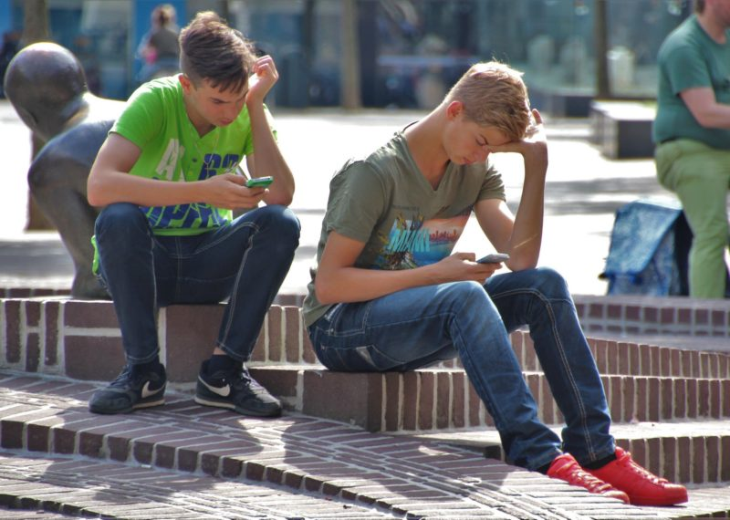 two young people sitting watching the phone in a park