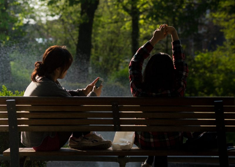 two girls sitting on a bench, one watching the phone and the other girl stretching