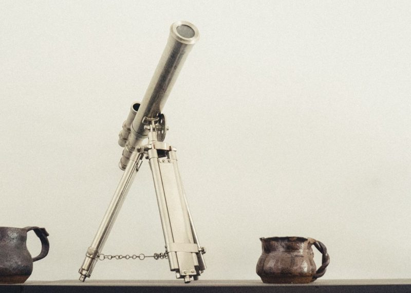 telescope, scale world, metal jars and a vase, wheat background