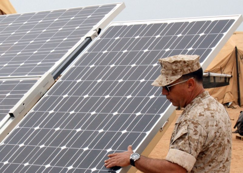 service members next to solar panels