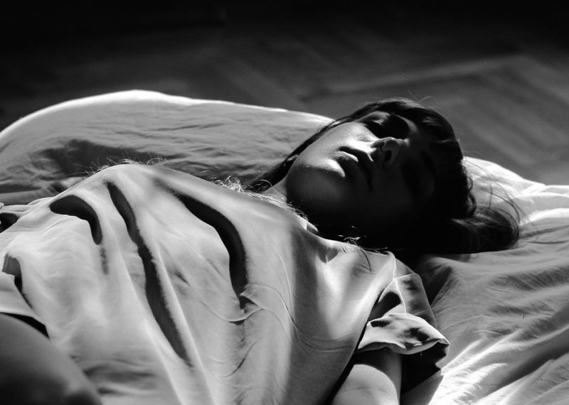 girl laying in a bed, black and white