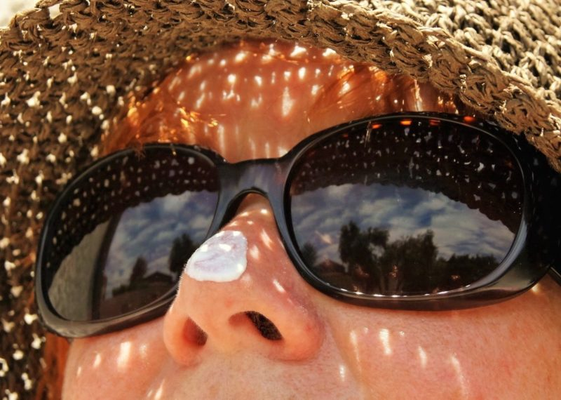 lady with a hat and sunglasses with solar protection cream