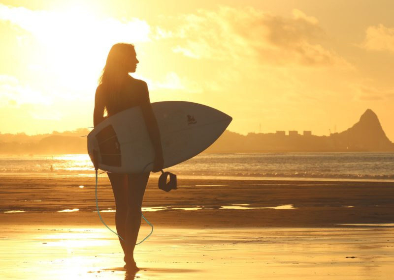surfer girl walking in the shore at sunset