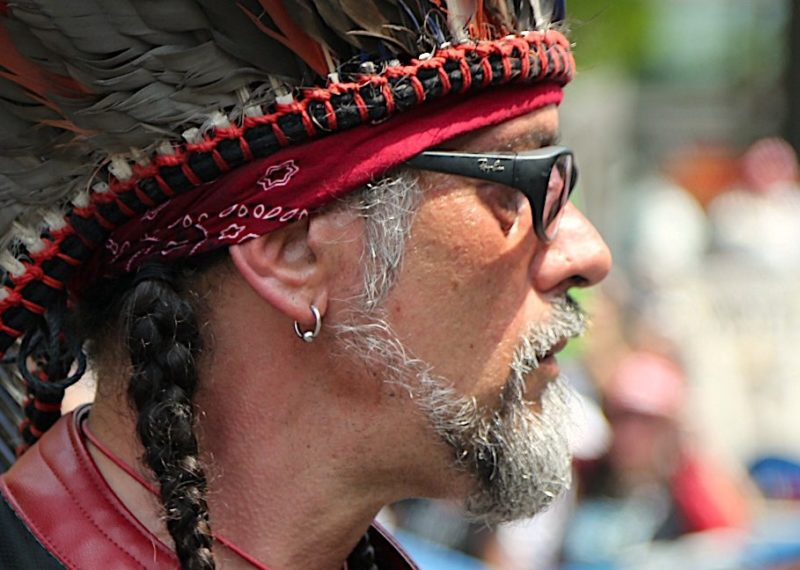 Native amercian protestor with headdress and glasses