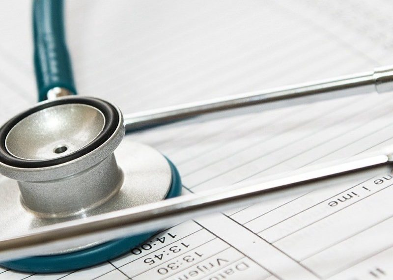 green stethoscope on clinic sheets