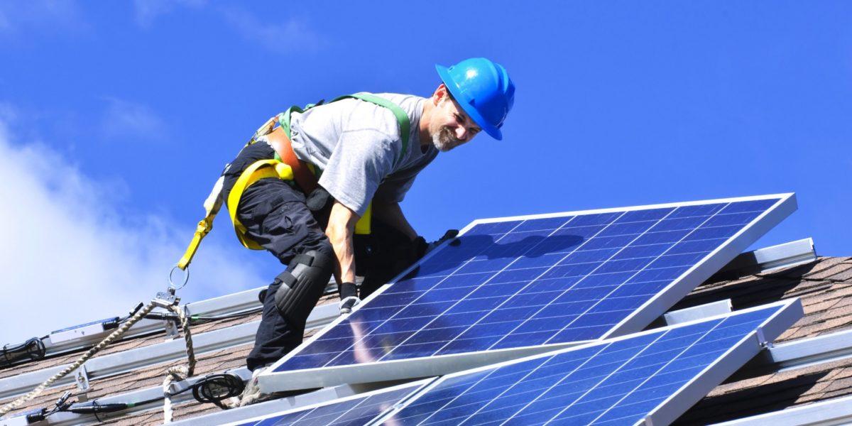 guy installing solar panels in the roof, blue helmet