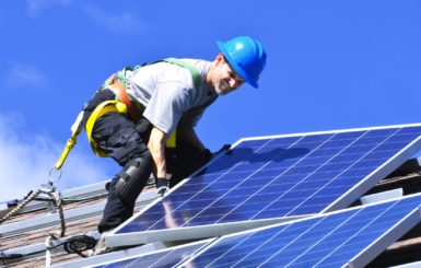 guy installing solar panels in the roof, blue helmet