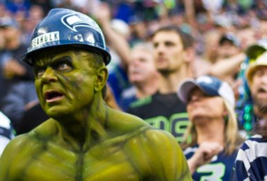 Seahawks fan with body paint like the hulk and a blue helmet with more fans of the team