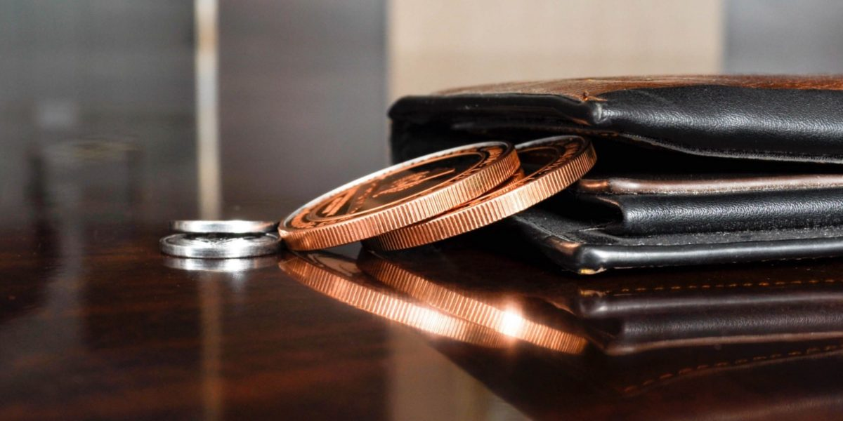 coins falling from wallet on a table