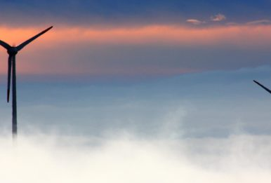 wind turbines foggy day at sunset