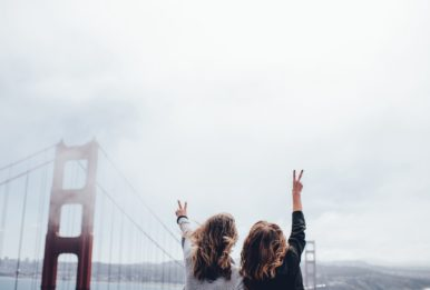 two girls taking a picture in a cloudy day in San Francisco Bridge
