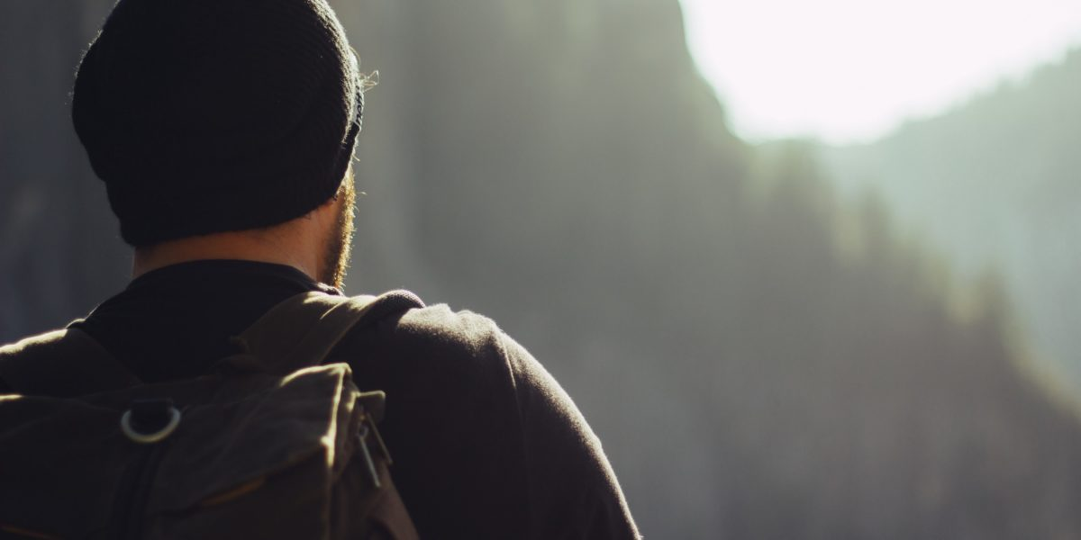 young man with his backpack watching the horizon.