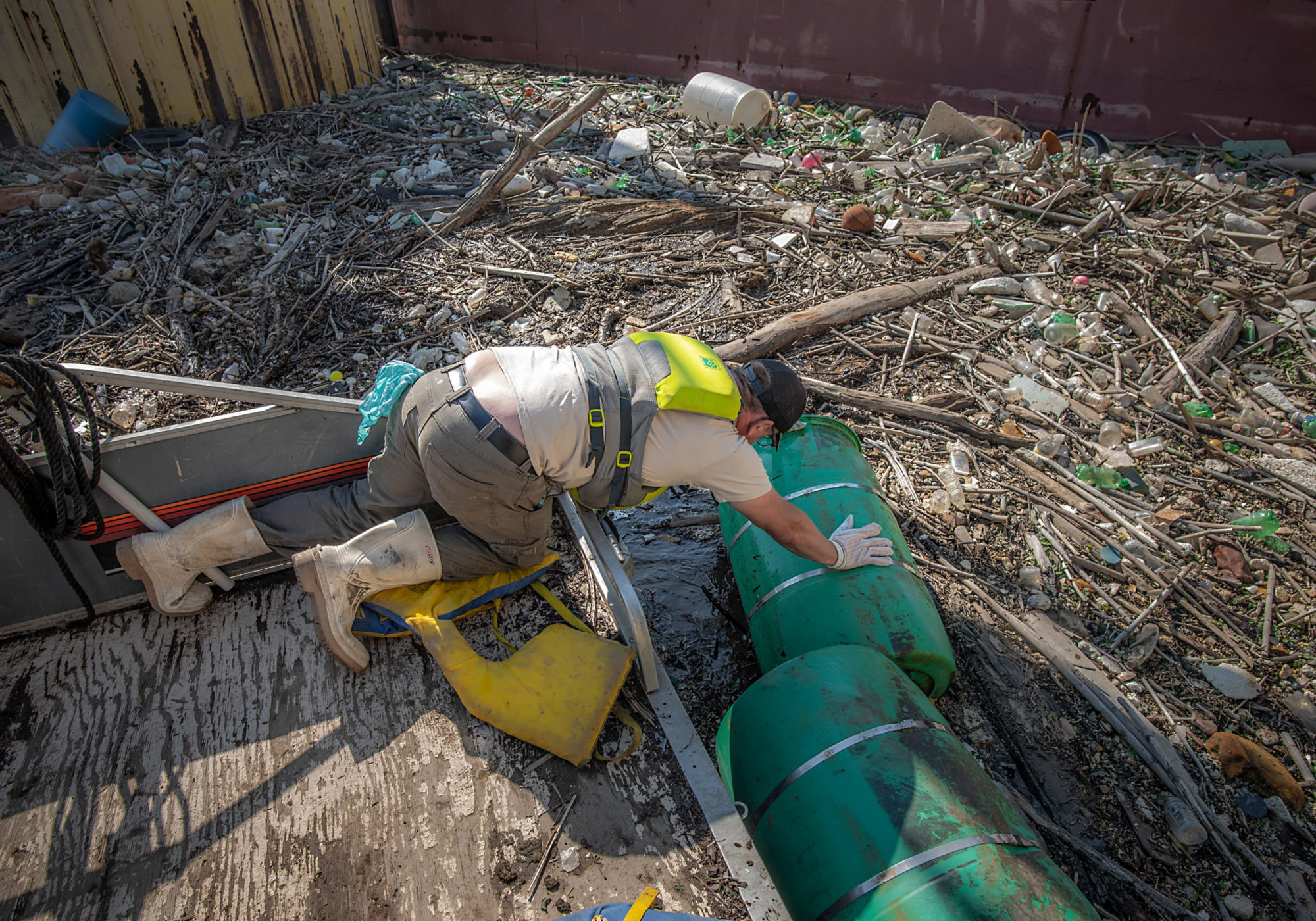 Evan Clark, a boat captain with the non-profit Allegheny CleanWays, tries to pull a plastic barrel from a debris island floating in the Monongahela River. CREDIT: Teake Zuidema/Nexus Media News