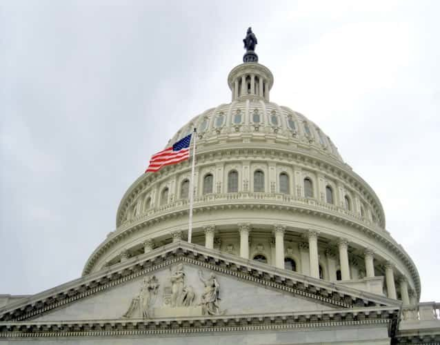 View of the dome of the Capitol building and the US flag in front of it