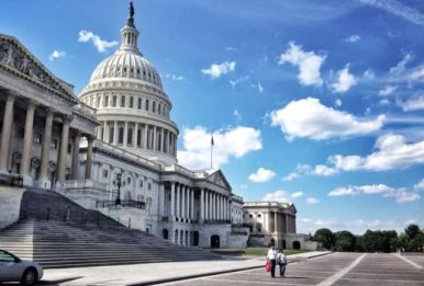 View of the Capitol building from the side with a beautiful blue sky