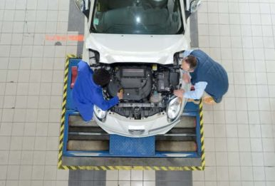 two men workin on a car at a factory