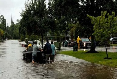 flood: pushing a boat on a street