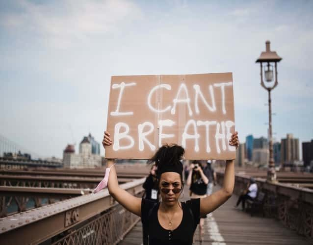woman of color holding a I can't breath sign