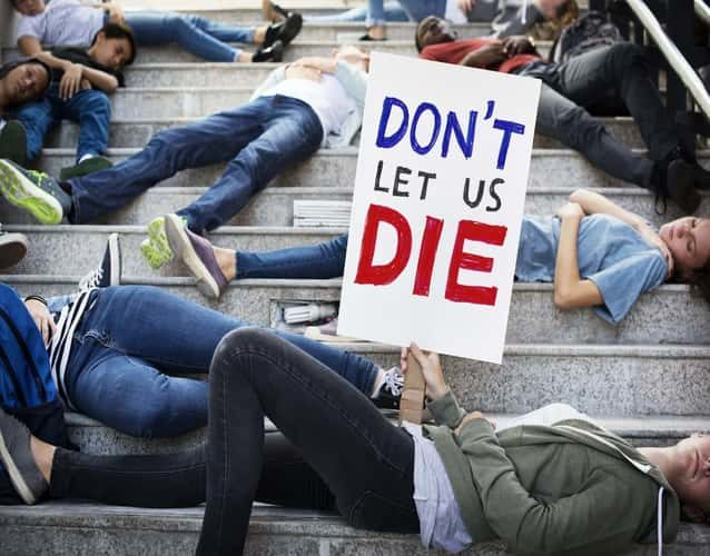 don't let us die sign held by a woman lying on steps during protest