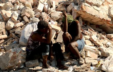 Haitian women sit on rubble from a collapsed building in Port-au-Prince, Haiti, after a 7.0-magnitude earthquake struck the region on January 12, 2010. Source: U.S. Air Force
