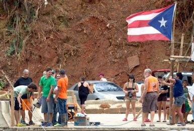 Villagers collect on bridge remnants to receive needed supplies in Utuado, Puerto Rico. Source: Andrea Booher, FEMA