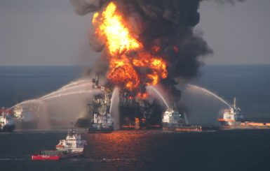 oil rig on fire with boats spraying water on it