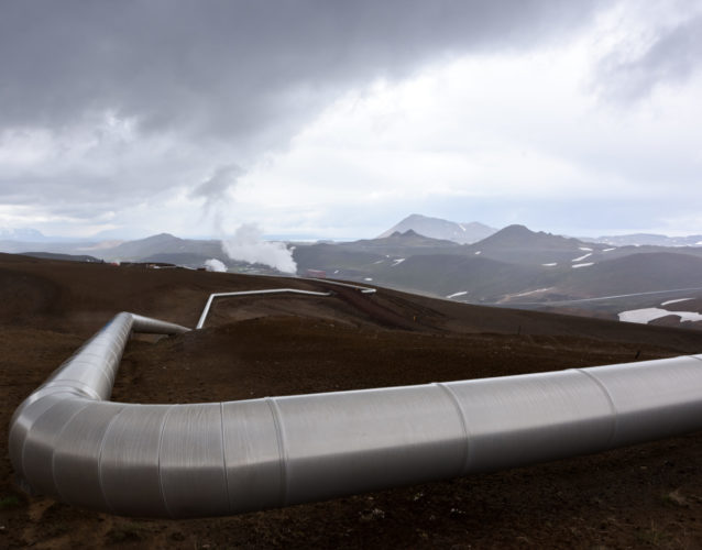 landscape with pipes in mountains. Geothermal energy in operations.
