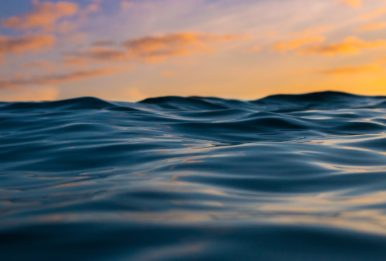 waves on the ocean with sunset colors