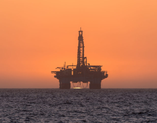 The sun is setting behind an oil drilling platform