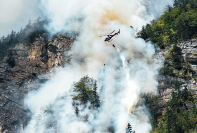 helicopter extinguishes forest fire on the slope of a mountain