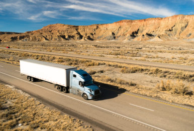 A trucker navigates the highway in his big rig